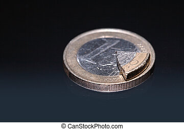 Dividend - Euro coin and coin\\\'s part lying on dark...