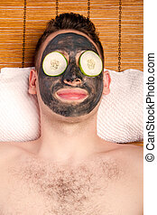 Male facial mask skincare - Man face with beauty treatment...