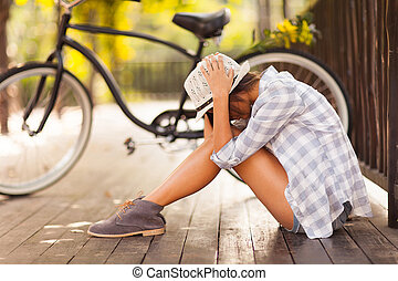 sad young woman sitting at the park next to bicycle
