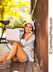 young woman using laptop outdoors - attractive young woman...