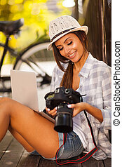 young photographer checking photos on her camera - smiling...