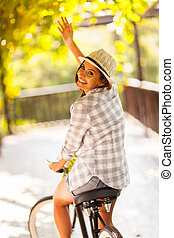 young woman riding her bike waving goodbye - cheerful young...