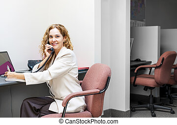 Smiling woman on telephone at office desk - Businesswoman on...