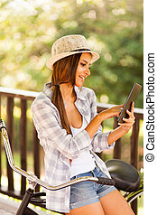 young woman reading emails on tablet computer outdoors -...
