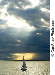Sailboat under dark clouds in bay of Thessaloniki, Greece.
