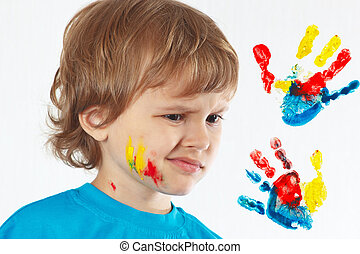 Dissatisfied boy with painted face on a background of hand...