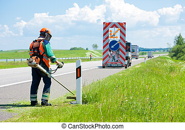 Road landscapers cutting grass around mileposts along the...