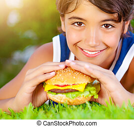 Happy boy eating burger - Closeup portrait of cute happy boy...