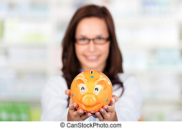 Pharmacist with piggybank - Smiling Pharmacist shows a...