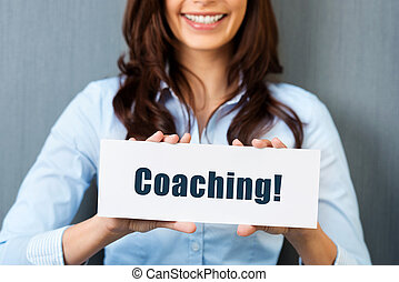 Coaching - Smiling woman showing white card with coaching...