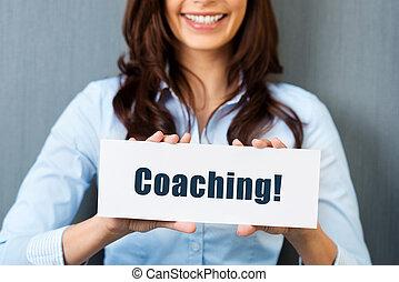Coaching - Smiling woman showing white card with coaching...