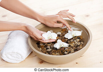 Orchids floating on water - Female hands placing white...
