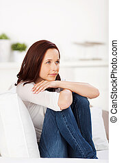 Pensive woman - Portrait of pensive woman sitting on couch...