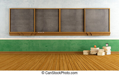 Empty vintage classroom with big blackboard and stacks of...