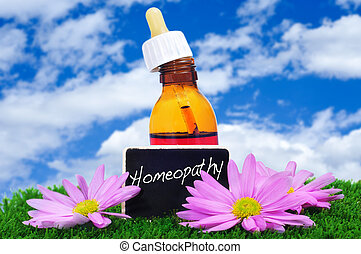 homeopathy - a dropper bottle and some purple flowers on the...