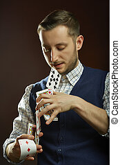 Skillful magician with playing cards - Skillful focused male...