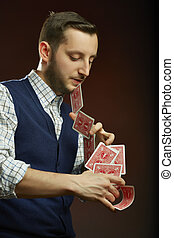 Playing cards trick - Skillful serious male magician...