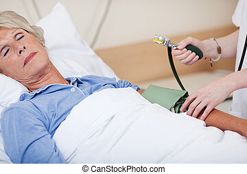 Doctor Measuring Blood Pressure In Hospital - Cropped image...