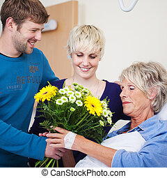 Children Giving Flower Bouquet To Mother In Hospital - Happy...