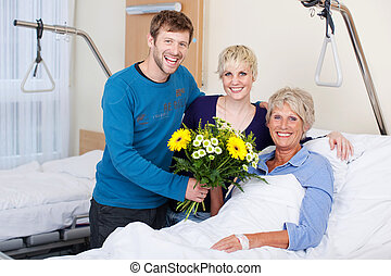 Children Giving Bouquet To Mother In Hospital - Portrait of...