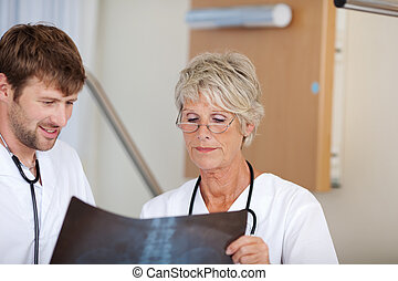 Male And Female Doctors Looking At Xray Report - Portrait of...