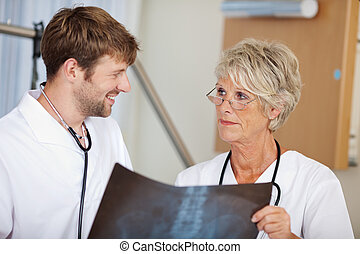 Male And Female Doctors Discussing Xray Report - Portrait of...