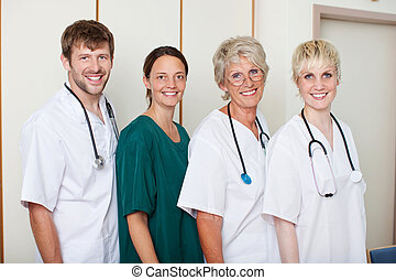 Confident Doctors Team Smiling While Standing In Row -...