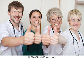 Doctors Team Showing Thumbs Up While Standing In A Row -...
