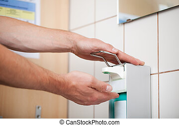 Doctors Hands Using Sanitizer Dispenser In Washroom -...