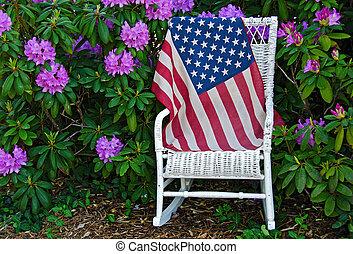 American flag in azalea garden - Flag on a wicker chair in a...