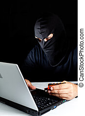 Data thief - Hooded thief stealing a laptop data