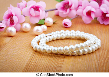 pearl bangles, with pink flower on wooden background