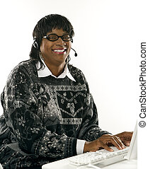 Woman wearing headset on computer.
