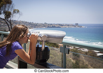 Young Girl Looking Out Over the Pacific Ocean with Telescope...