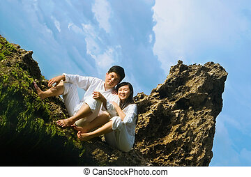 Young Couple On The Beach - Asian young couple sitting on...