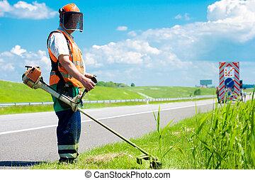 Road landscaper cutting grass
