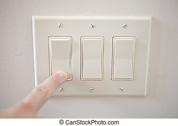 Light Switch - A finger switching off a light switch.