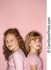 Girls standing back to back. - Caucasian female children...