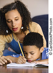 Mother helping son do homework. - Portrait of mom helping...