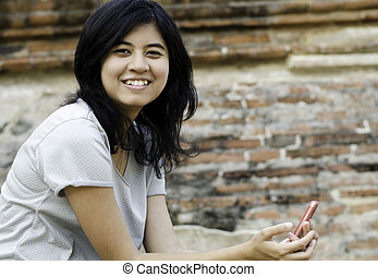 Smiling woman holds her phone