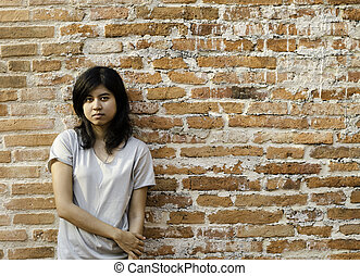 Young Asian woman against a Brick Wall