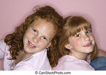Girls sitting back to back. - Caucasian female children...