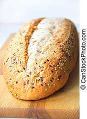 Bread with sesame and linseed on wooden board