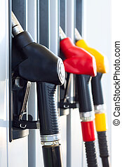Fuel pumps in a gas station - Several colored fuel hoses at...