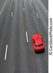 Red car moves fast on highway. - Vertical oriented image of...