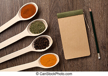 notebook and pencil for recipes and spices in spoons on...