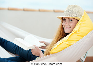 Smiling Woman Reading Book In Hammock - Happy relaxed young...