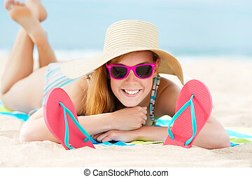 Smiling Woman Sunbathing On Beach - Portrait of a smiling...