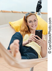 Relaxed Woman With Cellphone In Hammock - Relaxed young...