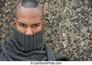 Portrait of an african american male fashion model with gray scarf covering face